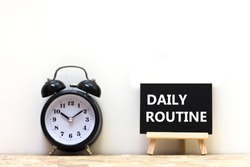 Alarm clock and daily routine words blackboard on desk white background.   Chalkboard write routine text on table for copy space.