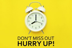 Alarm clock and Don't miss out hurry up text on yellow background.