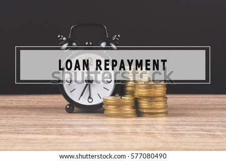Alarm clock and gold coin stack on wooden table and black background with text LOAN REPAYMENT.