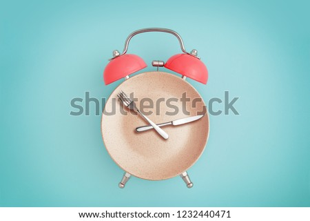 Alarm clock and plate with cutlery . Concept of intermittent fasting, lunchtime, diet and weight loss #1232440471
