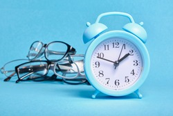 alarm clock and several different eye glasses on a blue background, glasses for children and adults, copy place, buy glasses concept