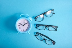 alarm clock and several different eye glasses on a blue background, glasses for children and adults, copy place, buy glasses concept, top view