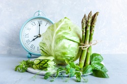 Alarm clock, Asparagus, microgreens, cucumber and cabbage - fresh green vegetables. Ketogenic diet, intermittent fasting, weight loss