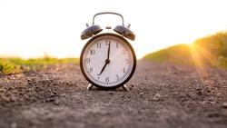 Alarm clock at sunset shows seven o'clock