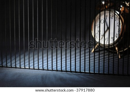 Alarm clock behind bars on dark background with copy space