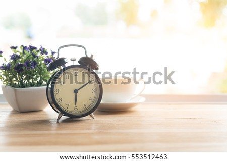 Alarm clock closeup have a good day with a cup of coffee and flower pots background in the morning sunlight. #553512463