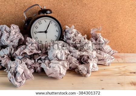 Alarm clock in a wastepaper  concept for a time waste of time with cork board texture background #384301372