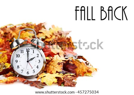 Alarm clock in colorful autumn leaves isolated against a white background with light shadow and shallow depth of field. Daylight savings time concept. #457275034