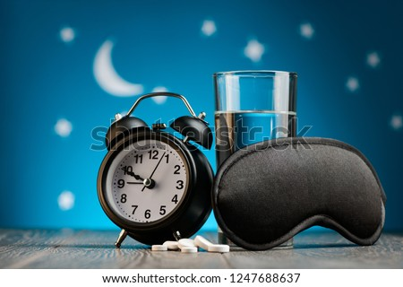 Alarm clock, mask, sleeping pills and glass of water. Fighting with insomnia for a good night rest.