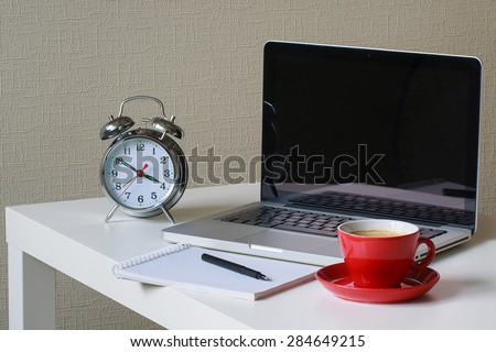 alarm clock, note book with black pen on it, red cup of coffee and silver laptop on the table