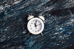 alarm clock on a dark background. copy space. flat lay. The concept of time, delay, morning rise, the appointed meeting