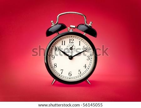 Alarm clock on a red background. Studio shot