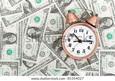 Alarm clock on a stack of dollars, reflecting time and money
