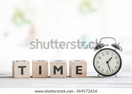 Alarm clock on a wooden desk with the word time #364572656