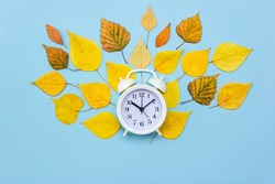 Alarm clock on blue background decorated with colorful fallen leaves. Autumn time concept. Selective focus. Copy space, flat lay