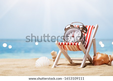 Alarm Clock On Deck Chair On Sunny Tropical Beach Foto stock ©