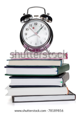 Alarm clock on notepads and books. Isolated on white background