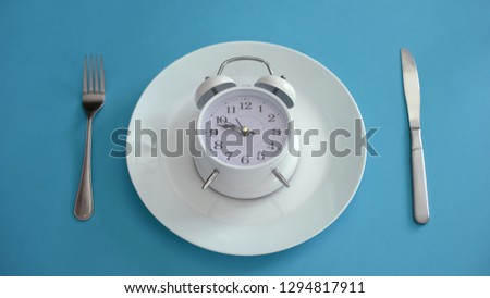 Alarm clock on plate, adhere to diet time, proper nutrition, discipline, closeup #1294817911