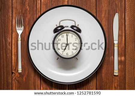 Alarm clock on plate with knife and fork on wooden background. Weight loss or diet concept #1252781590