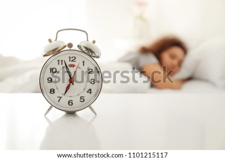 Alarm clock on table in bedroom of beautiful young woman. Morning time