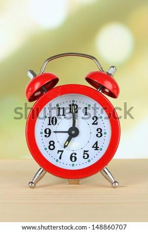 Alarm clock on table on light background