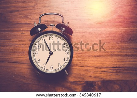 Alarm clock on teak wood background. Vintage filter. #345840617