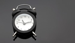 Alarm clock on the black background. Copy space