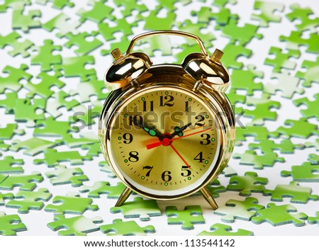 alarm clock on the green puzzle