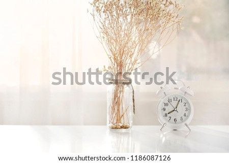 Alarm clock on the table in a white room with light orange.