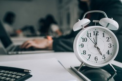 Alarm clock on wooden table with business discussion people group or meeting team background,Time concept at early morning or overtime in evening