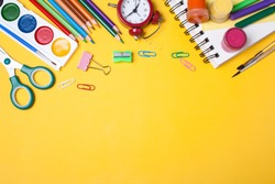 Alarm clock, paint, pencils and scissors. School accessories on a yellow background. View from above