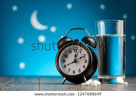 Alarm clock, pills and glass of water on a bedside table. Insomnia, treatment for sleepless nights.