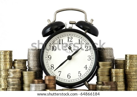 Alarm clock standing with coins on metal plate