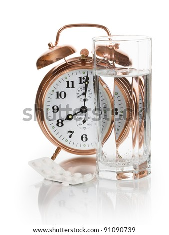 Alarm clock, tablets and glass of water on white background