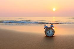 Alarm clock vintage with sunrise on beach