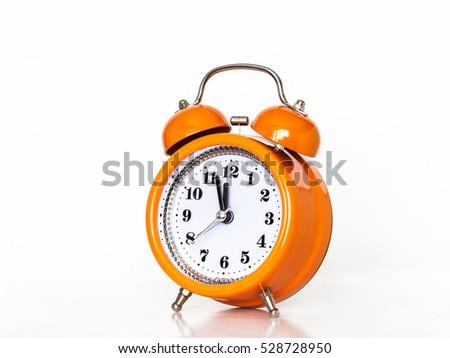 Alarm clock, watch hands showing midnight or noon.