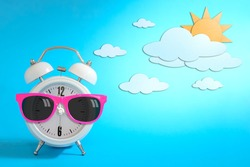 Alarm clock wearing sunglasses on day sky paper craft., Daytime concept.