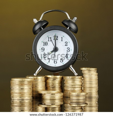 Alarm clock with coins on dark background