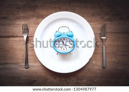 Alarm clock with fork and knife on the table. Time to eat #1304987977