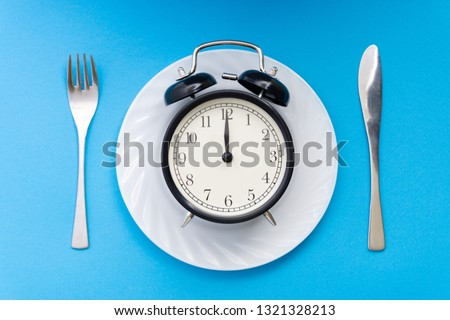 Alarm clock with fork and knife on the table. Time to eat, Breakfast, Lunch Time and Dinner concept. #1321328213