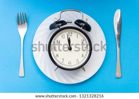 Alarm clock with fork and knife on the table. Time to eat, Breakfast, Lunch Time and Dinner concept. #1321328216