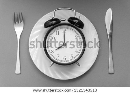 Alarm clock with fork and knife on the table. Time to eat, Breakfast, Lunch time and dinner concept. Black and White Concept #1321343513