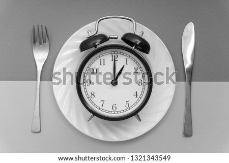 Alarm clock with fork and knife on the table. Time to eat, Breakfast, Lunch time and dinner concept. Black and White Concept #1321343549