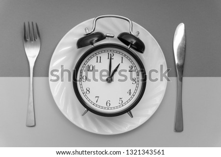 Alarm clock with fork and knife on the table. Time to eat, Breakfast, Lunch time and dinner concept. Black and White Concept #1321343561