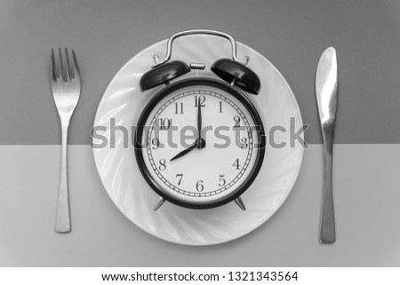 Alarm clock with fork and knife on the table. Time to eat, Breakfast, Lunch time and dinner concept. Black and White Concept #1321343564