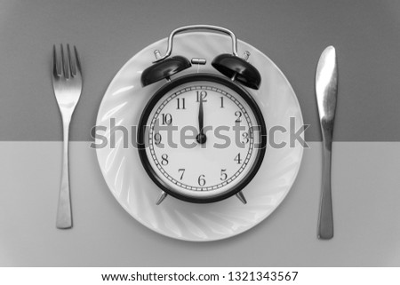 Alarm clock with fork and knife on the table. Time to eat, Breakfast, Lunch time and dinner concept. Black and White Concept #1321343567