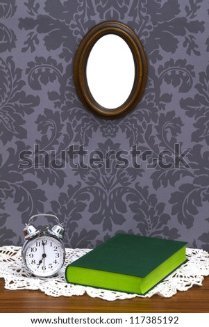 Alarm clock with green book on table cloth