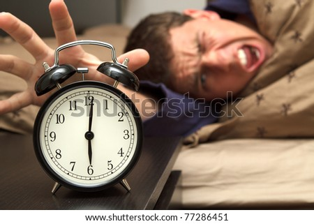 Alarm clock with male model in bed in background. Shallow depth of field. - stock photo