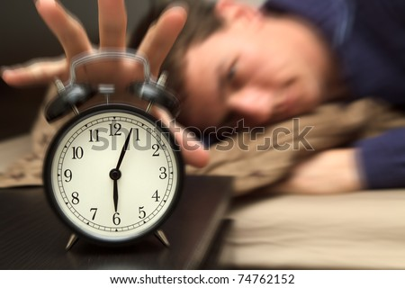 Alarm clock with male model in bed in background. Shallow depth of field, motion blur to show critical realization