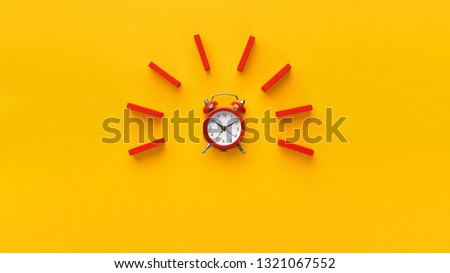 Alarm clock with red wooden dominoes on yellow background. Minimalism concept, panorama with empty space